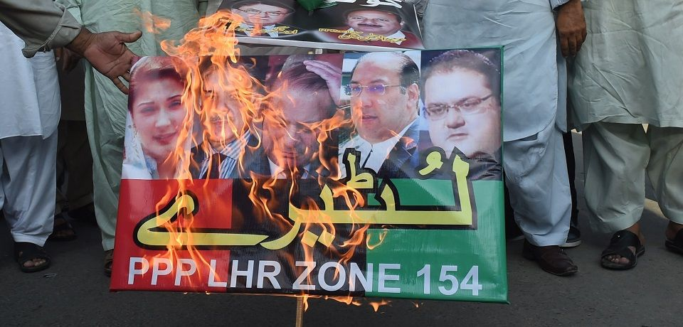 supporters of the pakistan peoples party ppp burn posters bearing the image od prime