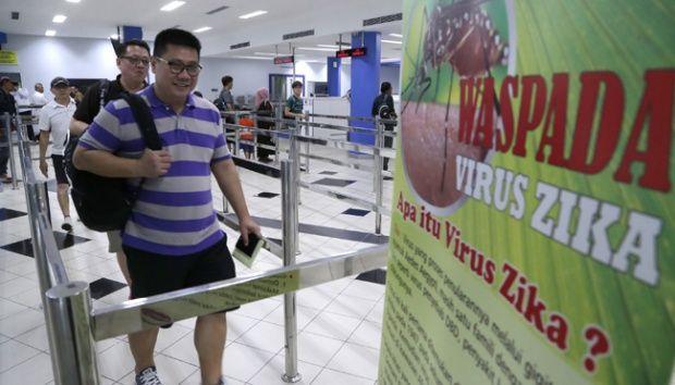 penumpang kapal ferry dari singapura melewati poster himbauan kewaspadaan terhadap penyebaran virus zika di pelabuhan internasional
